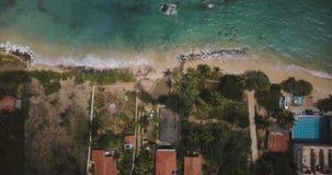 Tiro aéreo del Lockdown de las casas exóticas del centro turístico de costa del océano con las palmeras, ondas que lavan la playa metrajes