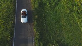 Tiro aéreo del montar a caballo convertible blanco del coche a través del camino rural vacío Cuatro mujeres irreconocibles jovene almacen de metraje de vídeo
