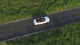Tiro aéreo del montar a caballo convertible blanco del coche a través del camino rural vacío Cuatro mujeres irreconocibles jovene metrajes