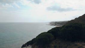 Tiro aéreo del vuelo sobre la colina y el camino con el mar Mediterráneo en el fondo metrajes