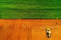 Tiro aéreo do fazendeiro com um trator no campo agrícola fotos de stock royalty free