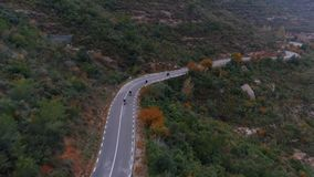 Tiro aéreo do grupo da motocicleta na estrada da montanha filme