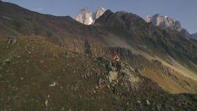 Tiro aéreo do lento-movimento de montanhas de escalada de um homem em um dia ensolarado no outono video estoque