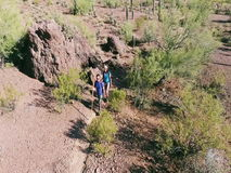 Tiro aéreo do movimento lento dos caminhantes no deserto do sudoeste filme