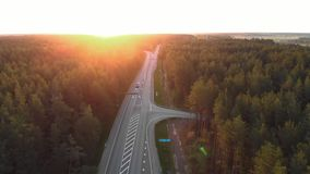 Tiro aéreo do nascer do sol da estrada fora da cidade em uma floresta do campo com cartões e caminhões que passam a compra - siga video estoque