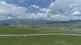 Tiro aéreo do voo sobre um campo gramíneo em um vale da montanha vídeos de arquivo