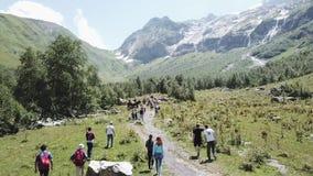 Tiro aéreo do zangão do voo que caminha o grupo que anda na fuga de montanha Grupo do turista que viaja no vale da montanha filme