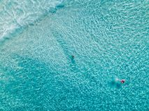 Tiro aéreo dos nadadores em uma praia bonita com água azul e a areia branca - águas profundas foto de stock