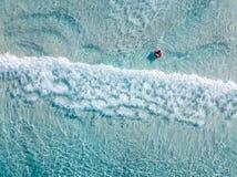 Tiro aéreo dos nadadores em uma praia bonita com água azul e a areia branca foto de stock