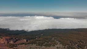Tiro aéreo El bosque del verde de la montaña en el primero plano, el pico de la montaña es rojo en color El volar sobre las nubes metrajes