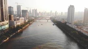 Tiro aéreo En el barco del flotador del río En el fondo es la ciudad y los puentes almacen de metraje de vídeo