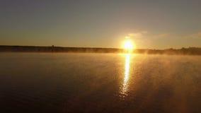 Tiro aéreo fantástico em 4k da névoa sobre o lago no por do sol filme