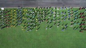 Tiro aéreo Grupo de pessoas no estádio que faz exercícios Aquecimento dos esportes de uma altura A vista da parte superior vídeos de arquivo