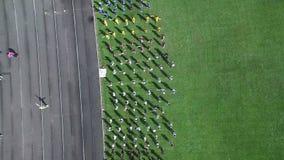 Tiro aéreo Grupo de pessoas no estádio que faz exercícios Aquecimento dos esportes de uma altura A vista da parte superior video estoque