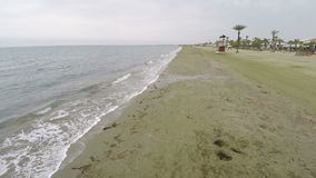 Tiro aéreo hermoso a lo largo de una playa en Chipre, estación baja, alga marina en la arena almacen de metraje de vídeo