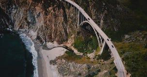 Tiro aéreo increíble de la visión superior de la carretera 1 en el puente de la cala de Bixby con las montañas que sorprenden y e metrajes