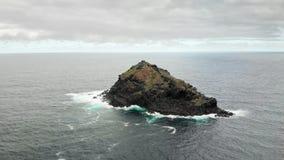 Tiro aéreo Isla de piedra de la lava volcánica congelada en las aguas azules del océano con una cruz católica en el top almacen de video