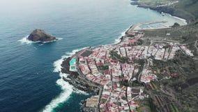 Tiro aéreo Litoral longo, ondas fortes Oceano azul e costa vulcânica Uma cidade pequena com casas brancas e os telhados vermelhos video estoque