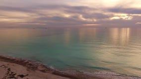 Tiro aéreo, mar tranquilo increíblemente hermoso en la luz de la puesta del sol con las porciones de nubes metrajes