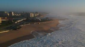 Tiro aéreo no por do sol sobre a praia e a cidade de Povoa de Varzim, Portugal no dia nevoento vídeos de arquivo