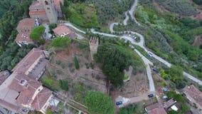 Tiro aéreo, pequeño pueblo italiano clásico magnífico en el paso elevado de la colina, en el centro de la naturaleza verde, hecho metrajes