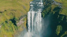 Tiro aéreo que voa sobre a cachoeira de Skogafoss em Islândia Dia ensolarado do arco-íris filme