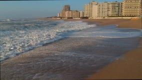 Tiro aéreo que vuela bajo sobre ondas en la playa arenosa vacía en Portugal almacen de video