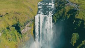 Tiro aéreo que vuela sobre la cascada de Skogafoss en Islandia Día soleado del arco iris metrajes