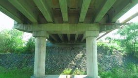 Tiro aéreo sob a simetria da ponte com base da rocha 4K vídeos de arquivo
