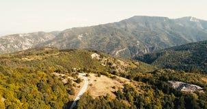Tiro aéreo sobre a estrada pequena nas montanhas em Sunny Day vídeos de arquivo