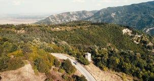 Tiro aéreo sobre a estrada pequena nas montanhas em Sunny Day With Moving Car video estoque