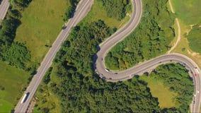 Tiro aéreo surpreendente do tráfego de carro na estrada da serpentina da floresta filme
