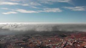 Tiro aéreo Un vuelo circular hermoso sobre las nubes volumétricas de la tempestad de truenos de la textura sobre un valle volcáni metrajes