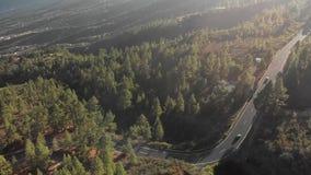 Tiro aéreo Voo sobre uma estrada nova da montanha do asfalto em que os carros se estão movendo Marcações de estrada novas Volta d filme