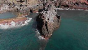 Tiro aéreo Vuelo circular en un día soleado sobre la costa del océano y la costa volcánica rocosa sobre las cuales azul metrajes