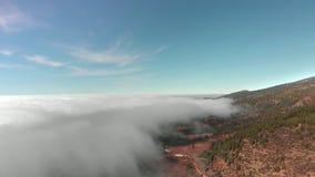 Tiro aéreo Vuelo hermoso sobre las nubes sobre el valle volcánico rojo En el marco de un bosque del verde almacen de video