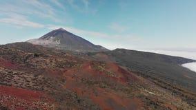 Tiro aéreo Vuelo sobre las nubes en el fondo del pico del volcán y del bosque alpino de las agujas del pino y almacen de video