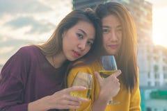 Tiro al aire libre de la gente joven que tuesta bebidas en un partido del tejado Amigas asiáticas jovenes que cuelgan hacia fuera Foto de archivo