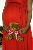 Tiro al aire libre de la mujer embarazada joven en el vestido rojo que se coloca con el juguete para su niño previsto y que mira  Imagenes de archivo