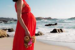 Tiro al aire libre de la mujer embarazada joven en el vestido rojo que se coloca con el juguete para su niño previsto y que mira  Foto de archivo