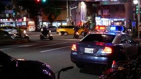 Tiro al aire libre de la noche de las luces de emergencia rojas y azules del coche policía almacen de video