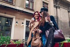 Tiro al aire libre de las mujeres jovenes que caminan en la calle de la ciudad y comiendo café Amigos que hablan y que se diviert Imagen de archivo