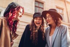 Tiro al aire libre de tres mujeres jovenes elegantes que hablan en la calle de la ciudad Amigos que ríen y que se divierten Fotos de archivo libres de regalías