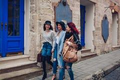 Tiro al aire libre de tres mujeres jovenes que caminan en la calle de la ciudad Amigos que hablan y que se divierten Imágenes de archivo libres de regalías
