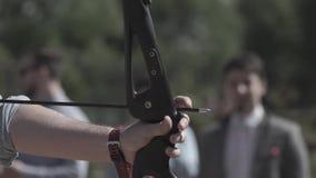 Tiro al arco practicante de la deportista Ciérrese encima de la mano del entrenamiento masculino del soldado con el arror y arque almacen de metraje de vídeo