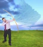 Tiro al arco practicante del hombre de negocios con el campo verde adentro Fotos de archivo