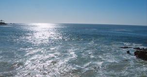 Tiro ancho aéreo perfecto de una playa de Malibu California con las ondas de agua blanca que se estrellan en la arena desde un pu metrajes