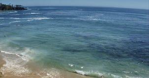 Tiro ancho aéreo perfecto de una playa de Malibu California con las ondas de agua blanca que se estrellan en la arena desde un pu almacen de metraje de vídeo