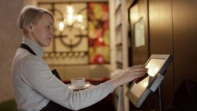 Tiro ancho del encargado que birla el terminal del pago del tacto como camarera que escoge encima de cuenta de la tabla para mant almacen de video