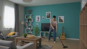 Tiro ancho del hombre que limpia el apartamento acogedor con el aspirador metrajes